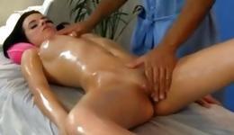 Fabulous brunette lying on massage bed getting her kinky body rubbed